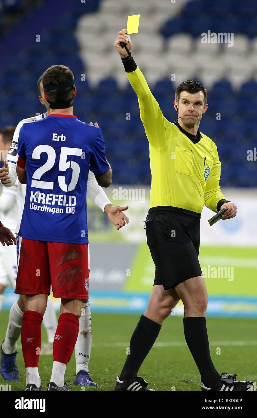 firo: 08.03.2019 Football, 3. Bundesliga, season 2018/2019 KFC Uerdingen 05 - Karlsruher SC referee Alexander Sather shows Mario Erb (# 25, KFC Uerdingen 05) the yellow card for handball and gives penalty for Karlsruhe. | usage worldwide - Stock Image