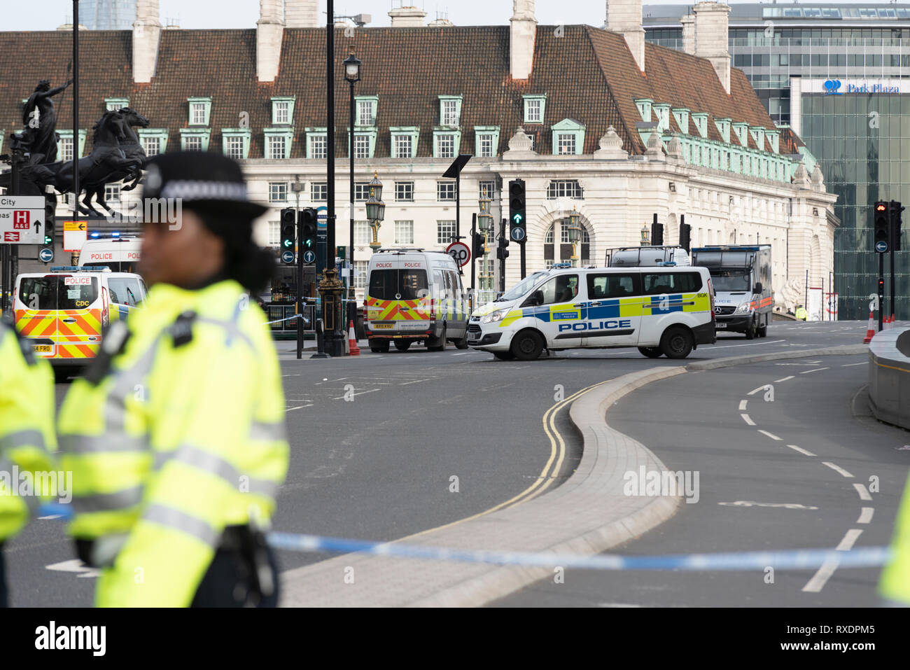 A suspicious car parked outside New Scotland Yard police headquarters on Victoria Embankment, Westminster, London, UK caused the police to lockdown and clear the the area around it and Westminster Bridge, including stopping river traffic on the Thames. Police broke the rear screen of the car to gain entry. Police cordoning off and clearing Westminster Bridge Road - Stock Image