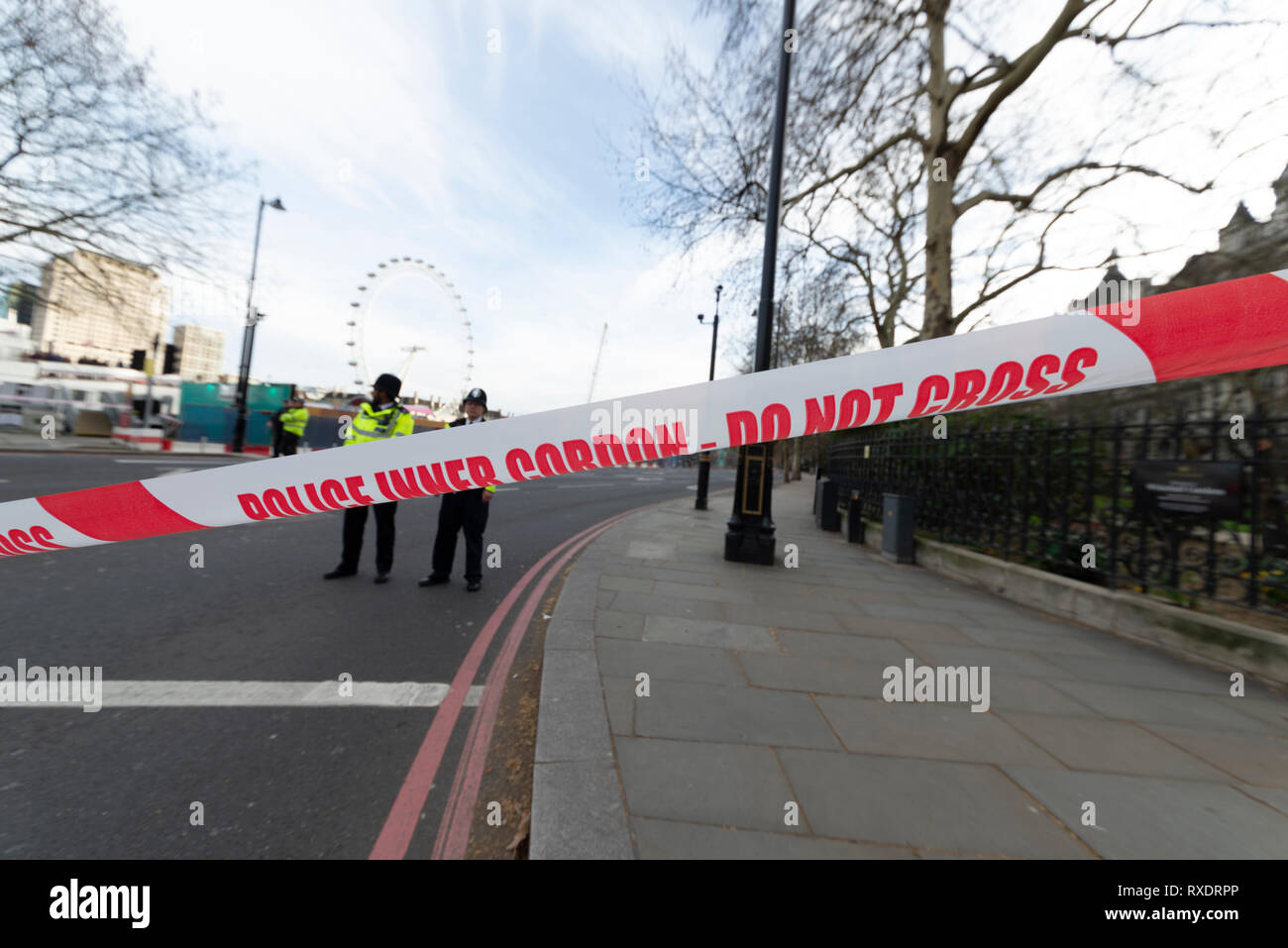 A suspicious car parked outside New Scotland Yard police headquarters on Victoria Embankment, Westminster, London, UK caused the police to lockdown and clear the the area around it and Westminster Bridge, including stopping river traffic on the Thames. Police broke the rear screen of the car to gain entry. - Stock Image
