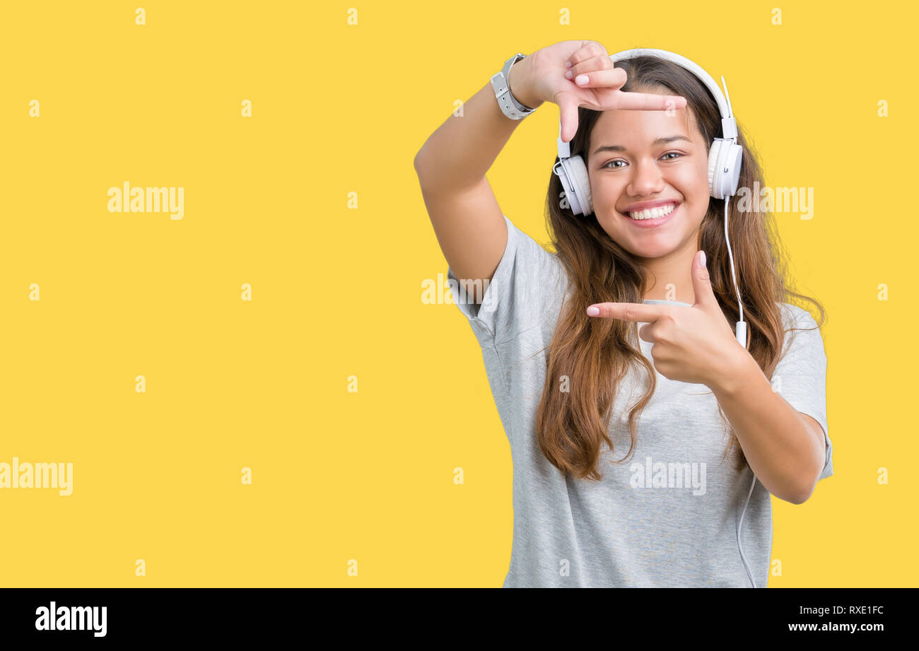Young beautiful woman wearing headphones listening to music over isolated background smiling making frame with hands and fingers with happy face. Crea Stock Photo