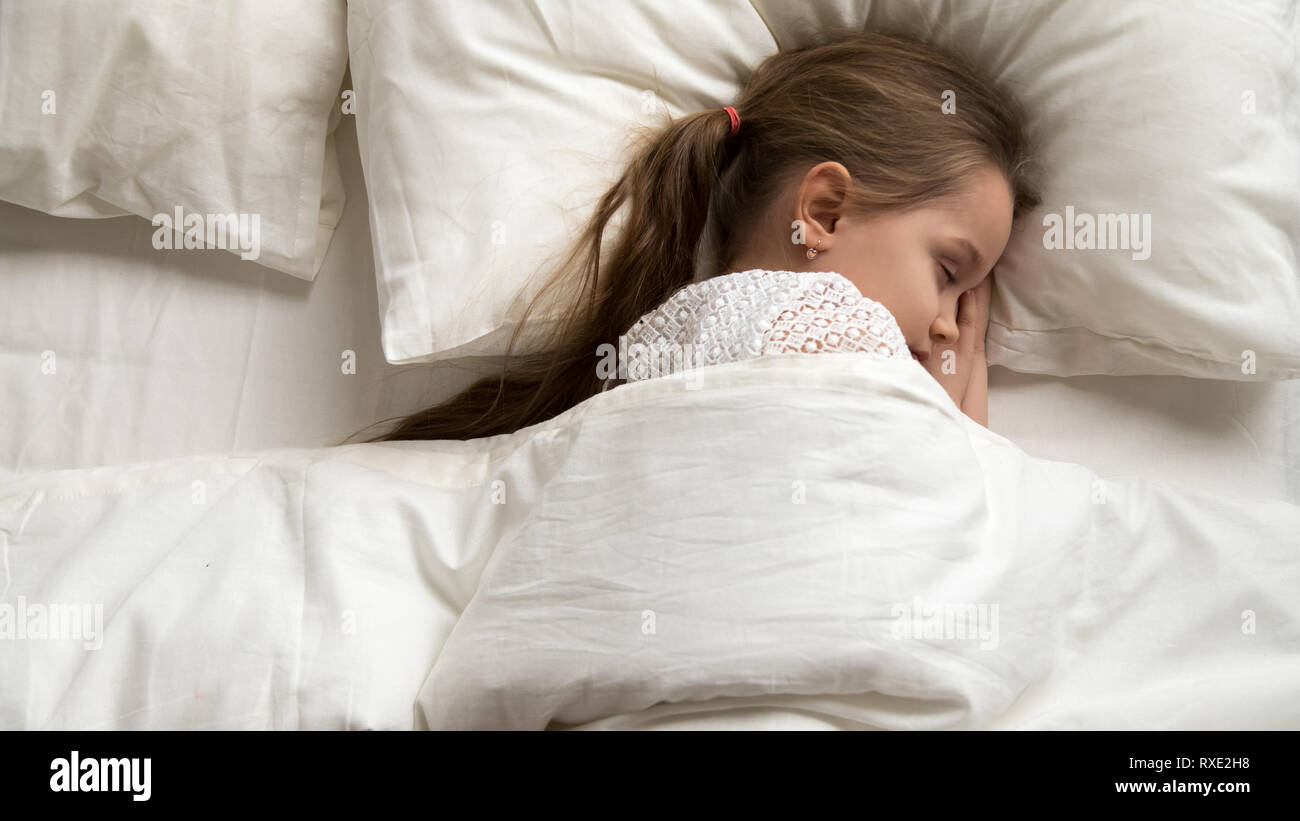 Adorable little girl sleeping alone in comfortable bed, top view - Stock Image