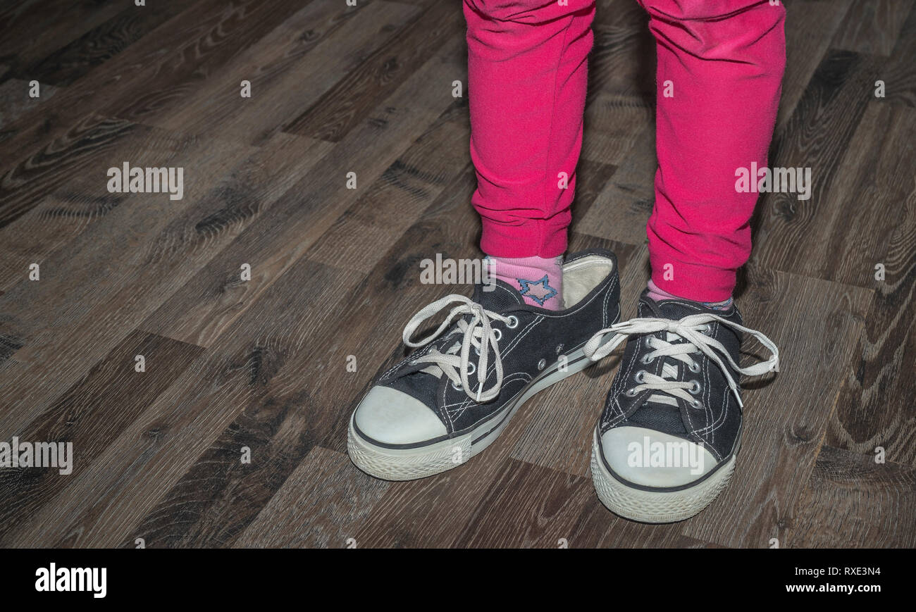 The child wears big black sneakers and boasts that he was grown up because he has great shoes - Stock Image