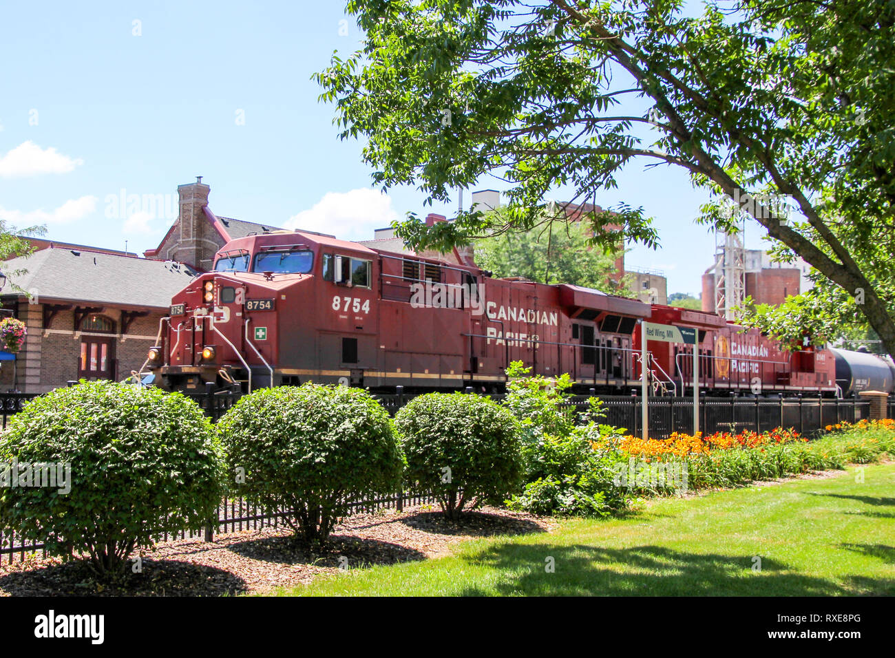 Locomotive passing Red Wing, MN train depot - Stock Image