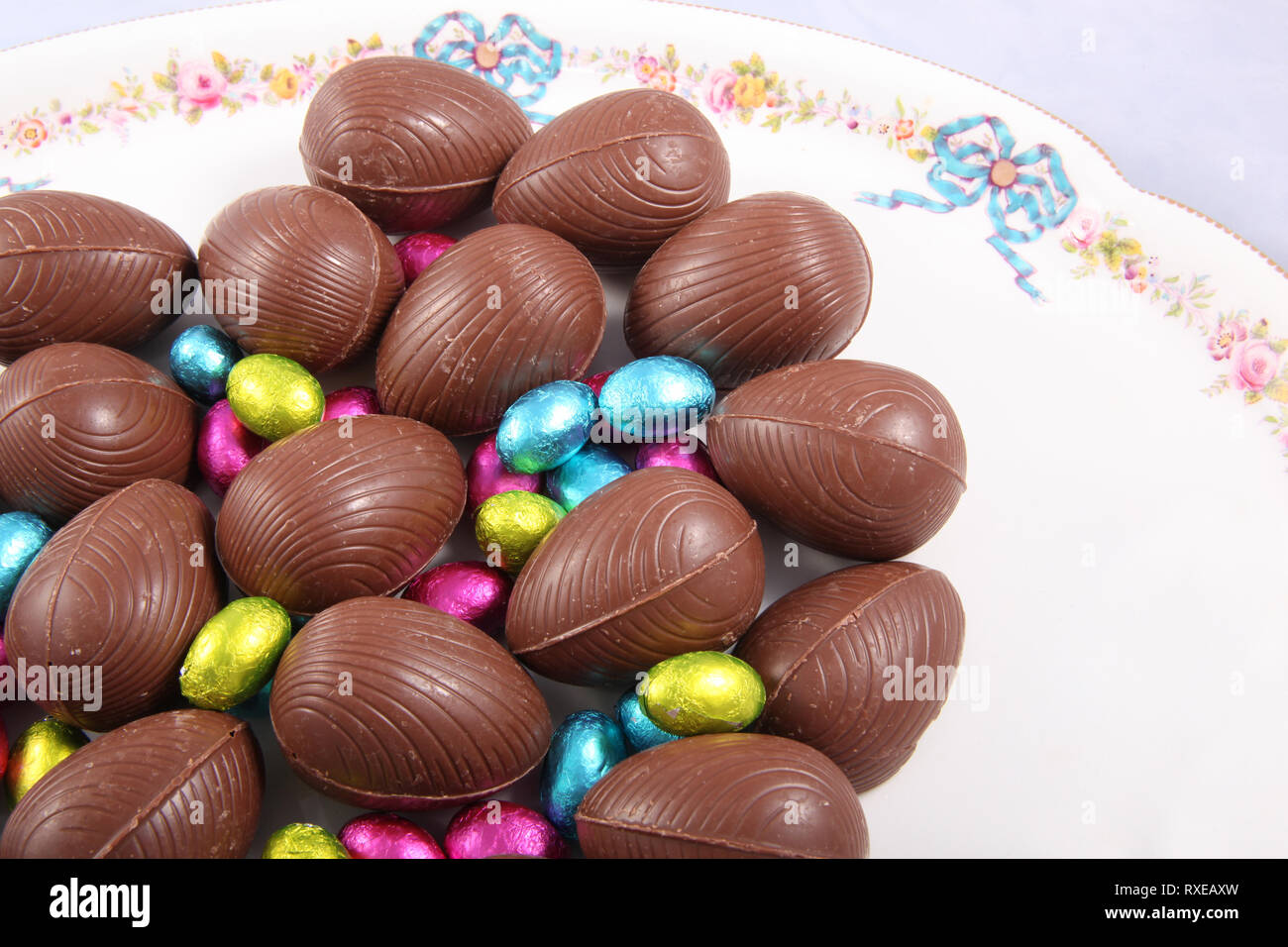 Chocolate easter eggs & colourful foil wrapped eggs on a white plate with a traditional flower design. Stock Photo