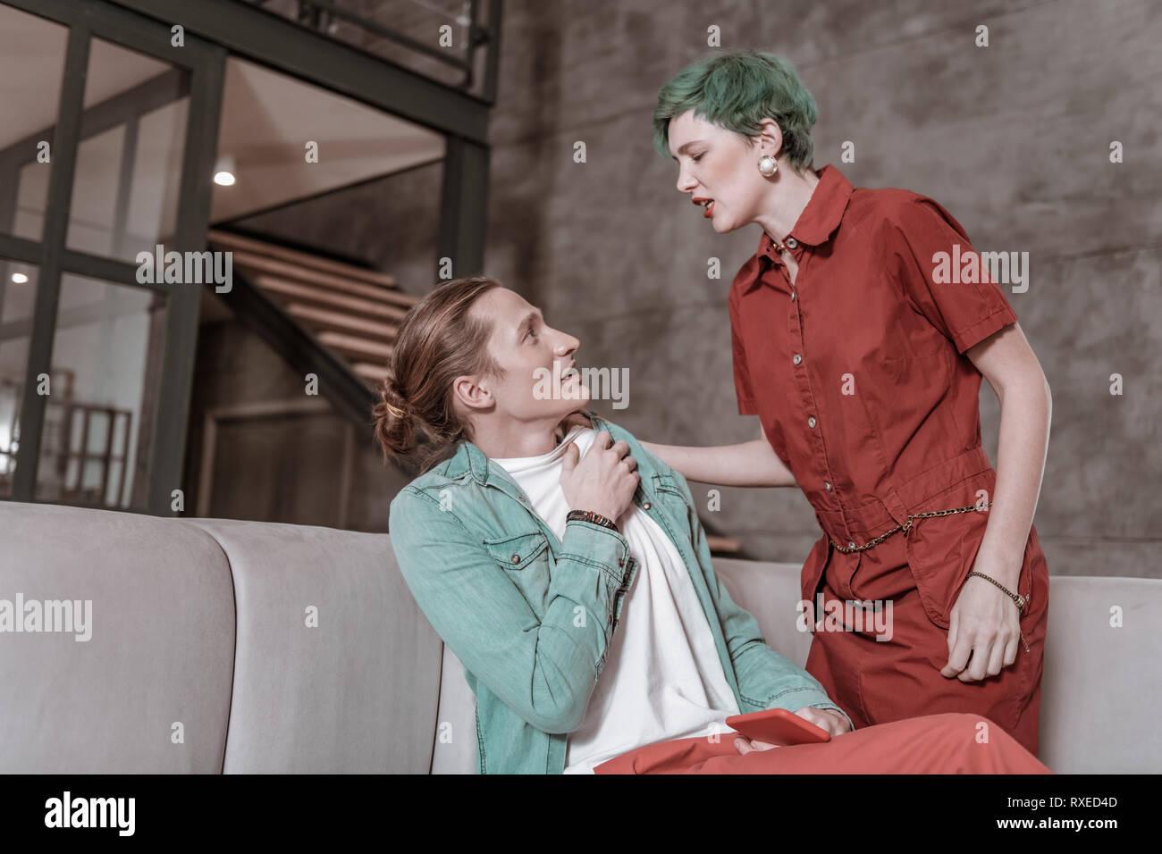 Girlfriend feeling jealous pushing her boyfriend cheating on her - Stock Image