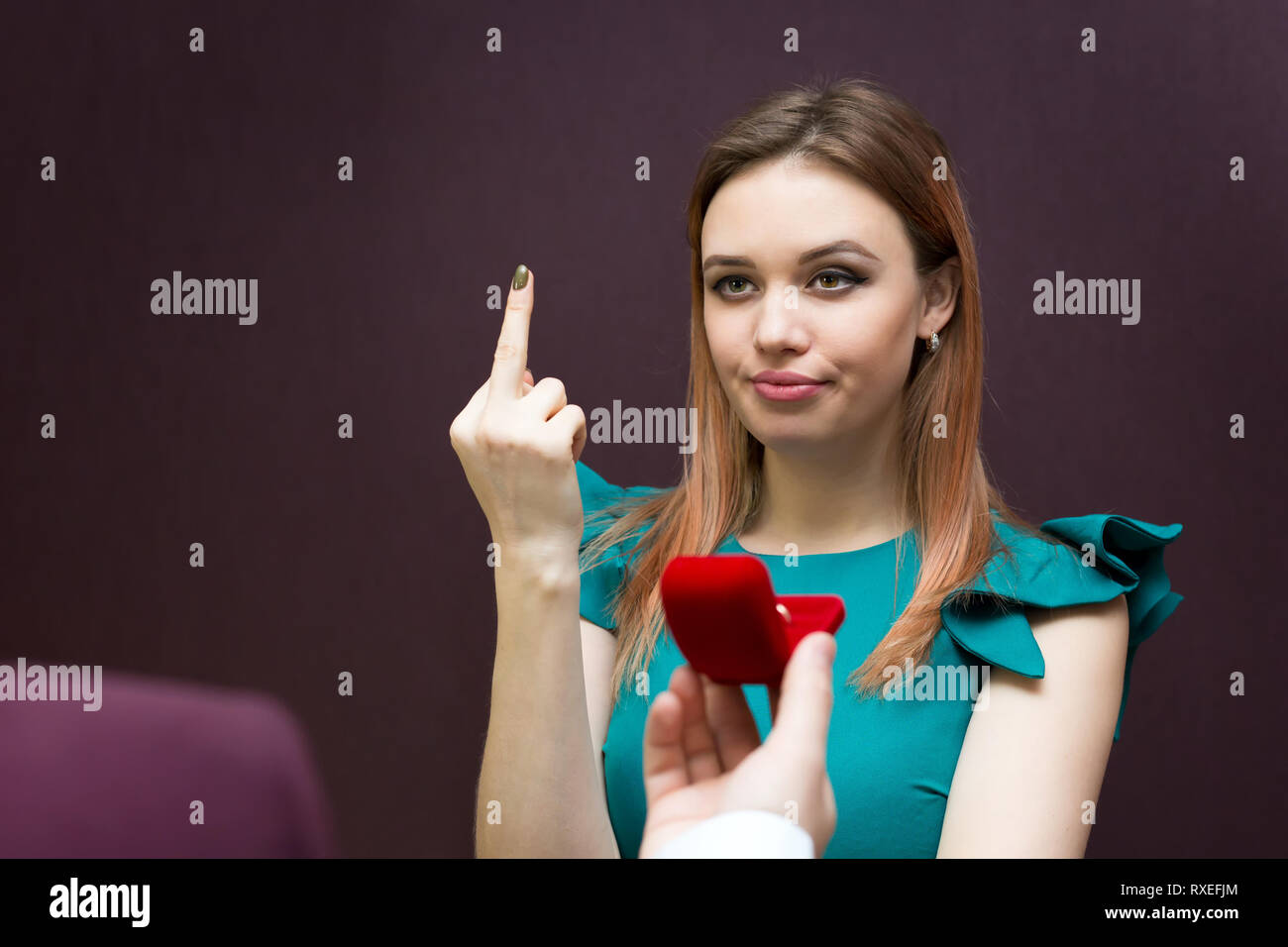 An evil woman refuses a man and shows a bad hand gesture. - Stock Image