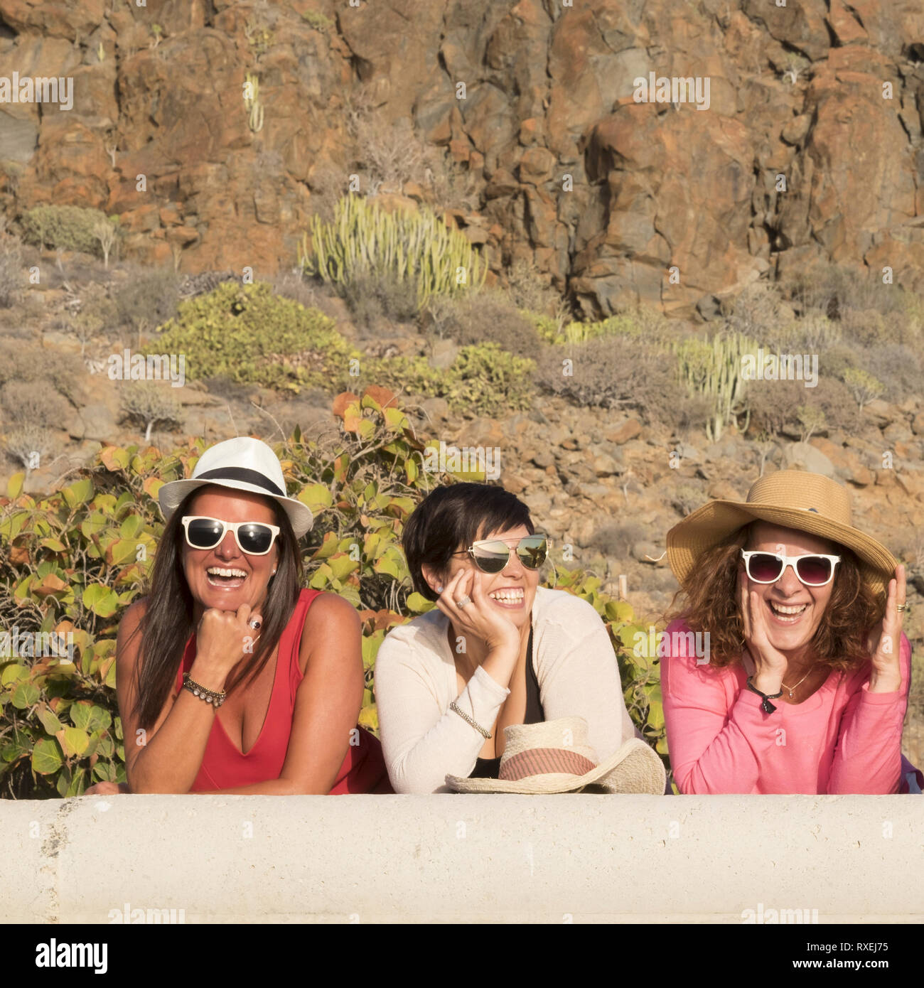 Happiness concept with three young friends women together with hats and sunglasses in summer day laughing and having fun - cheerful female people cauc - Stock Image