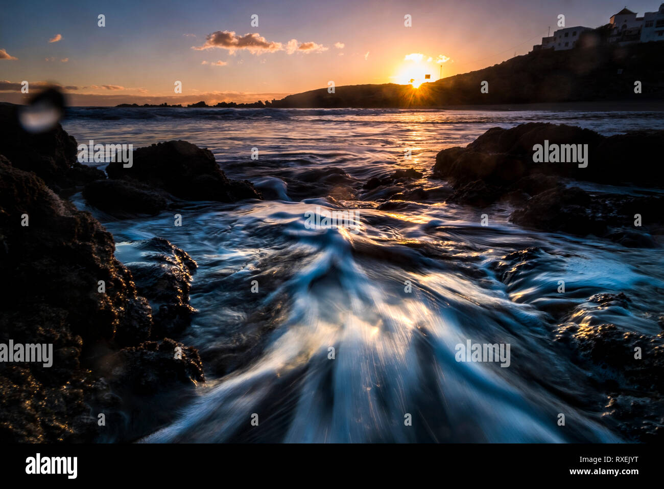 Motion effect with waves and water at the beach with sea and sunrise - vacation and landscape scenery concept - sunlight from sunrise and coloured sky Stock Photo