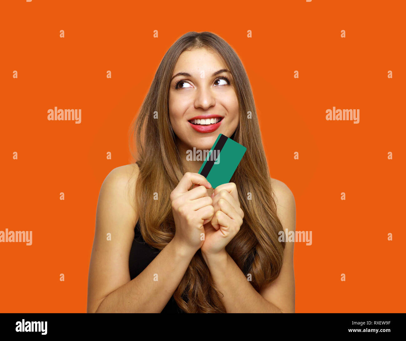 Pleased intrigued brunette woman in dress holding credit card and looking away over orange background - Stock Image