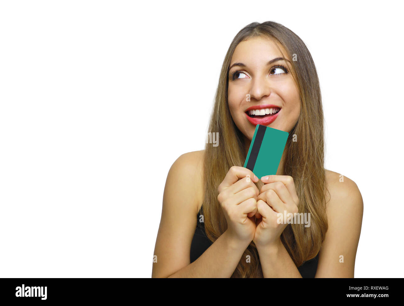 Pleased intrigued brunette woman in black dress holding credit card and looking away over white background - Stock Image