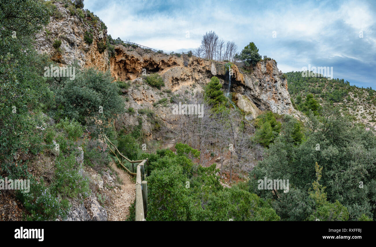 Track to caves and waterfall against cloudy sky - Stock Image