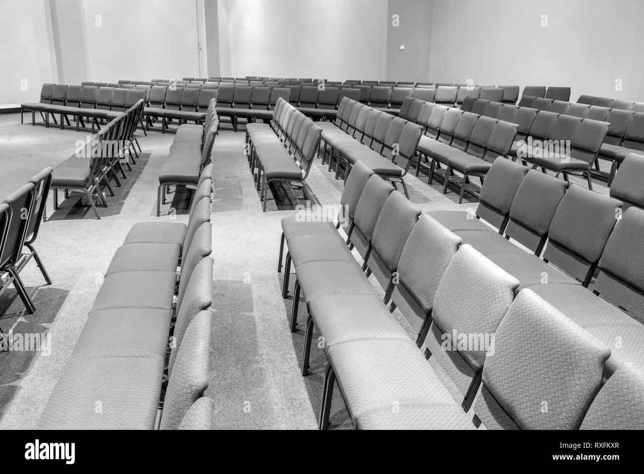 Horizontal black and white shot of empty auditorium seating standing at the side looking across. - Stock Image