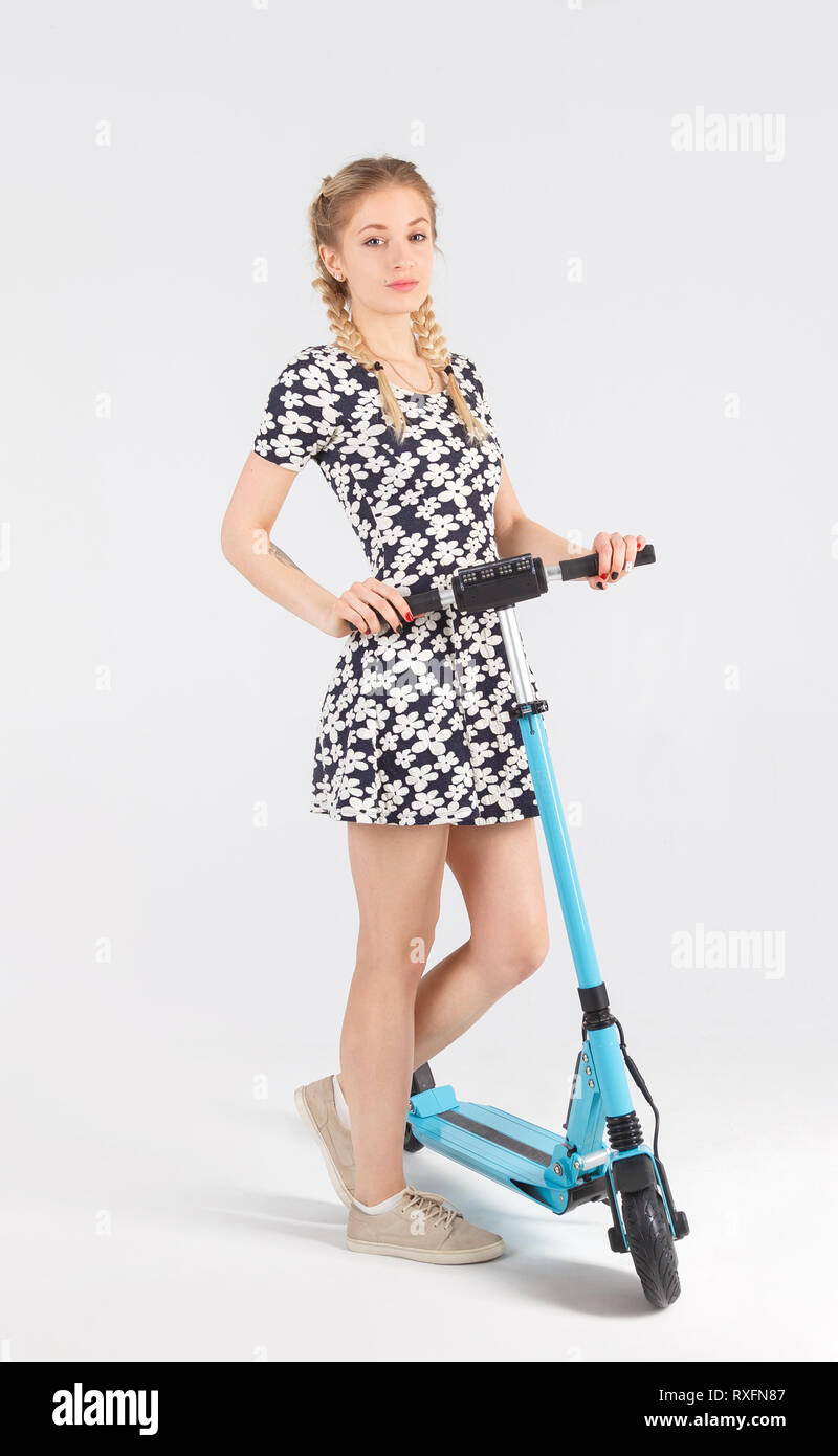 Full length portrait of girl in sundress with a scooter isolated on white background. - Stock Image