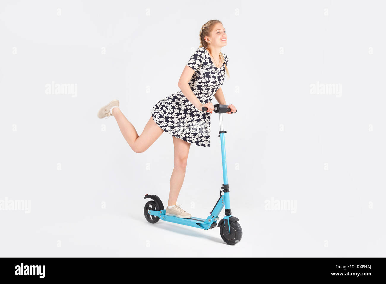 Beautiful woman in sundress ride a blue scooter on white isolated background. - Stock Image