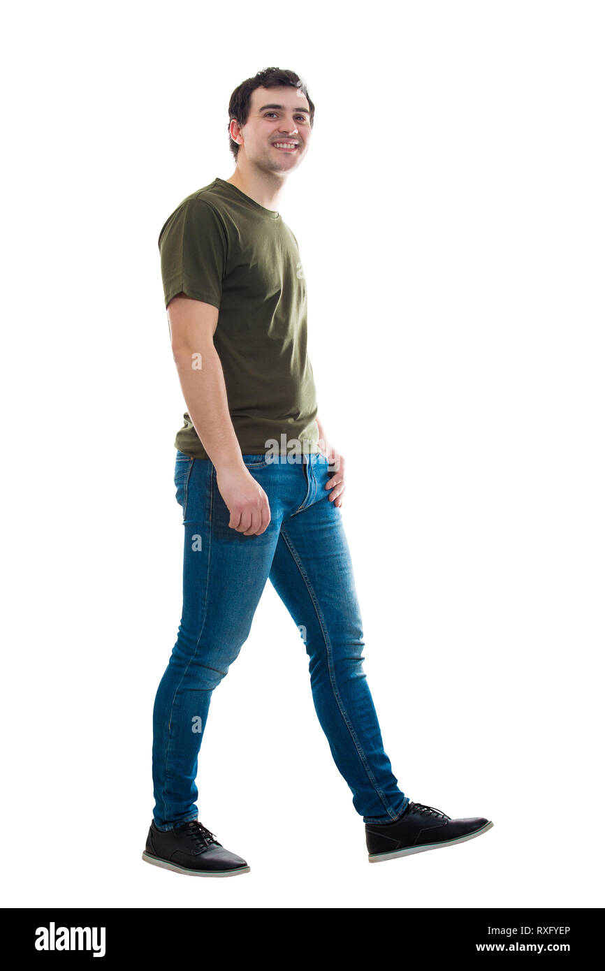 Full length side view of casual young man confident walking with hand in pocket isolated over white background. Motion shot making a step going ahead  - Stock Image