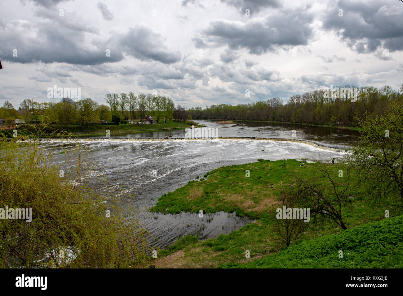 riverside landscape in latvia with dark water and dirty shore line. high water in spring with old wood and dirt - Stock Image