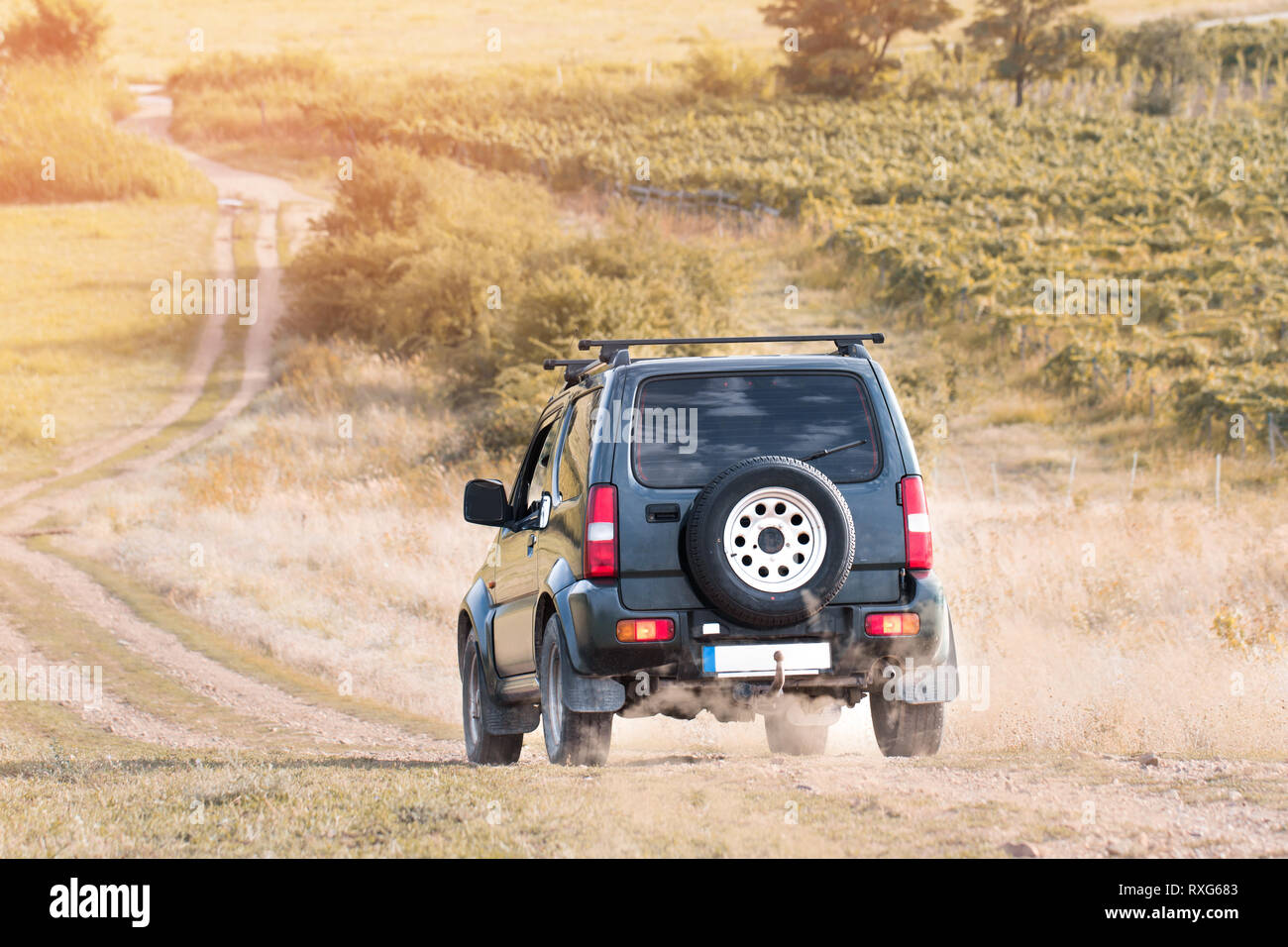 suv car offroad on dirt road in sunset - Stock Image