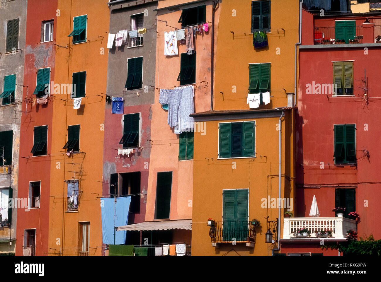 Multicolored facades marked by windows, shutters, balconies, and laundry hung out to dry decorate the vertical dwellings that overlook the boat harbor at Portovenere, Italy. Strong sunshine along the Mediterranean seacoast is a cause for frequent repainting of the exterior walls of these attached residences. This medieval fishing village on the Italian Riviera is among the most picturesque but lesser-known tourist towns in the Liguria region. Stock Photo