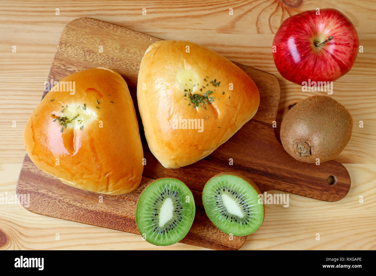 Top view of savory buns on wooden tray with apple and kiwi fruits - Stock Image