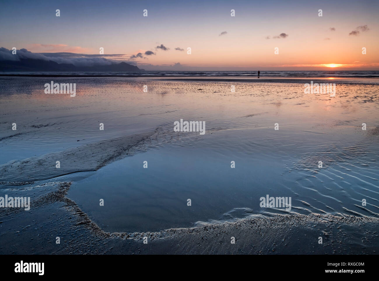 Lone Walker at sunset, Dinas Dinlle Beach, Dinas Dinlle, Gwynedd, North Wales, UK MODEL RELEASED Stock Photo