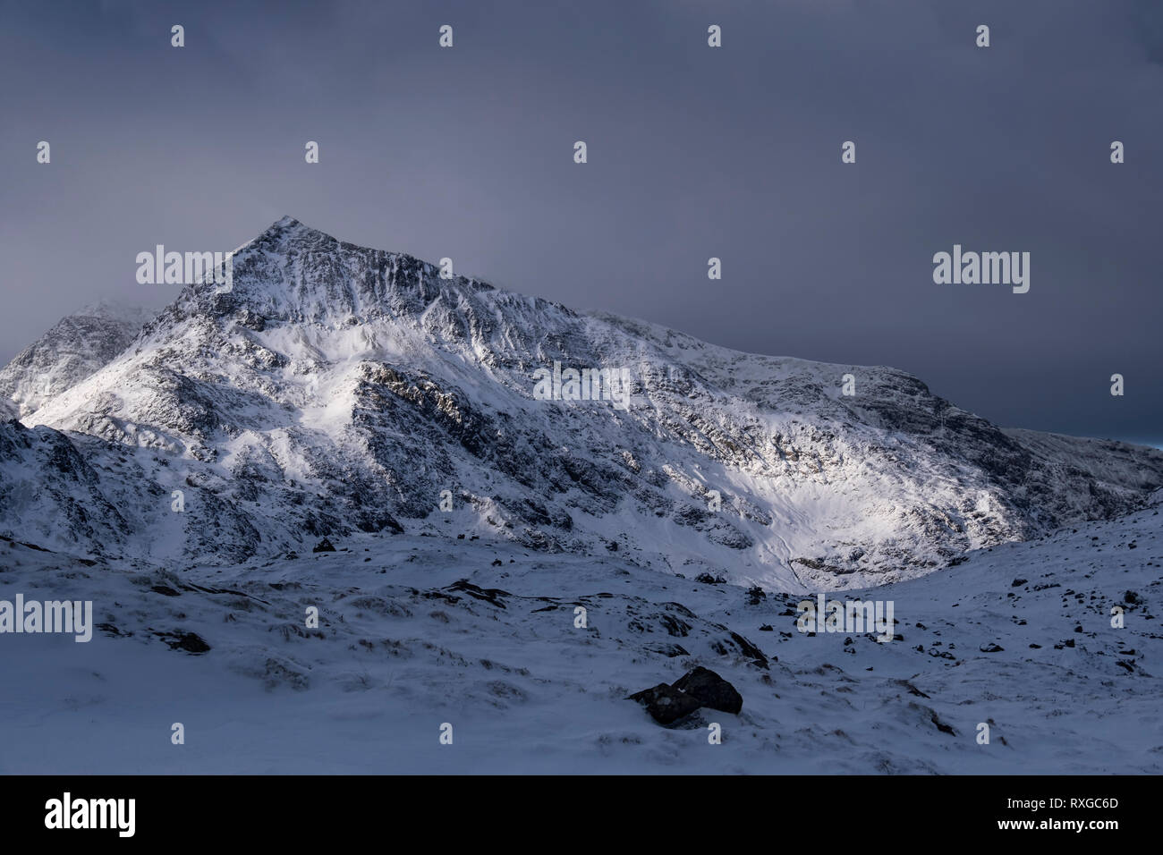Mountain Light, Crib Goch backed by Snowdon in winter, Snowdonia National Park, Gwynedd, North Wales, UK - Stock Image