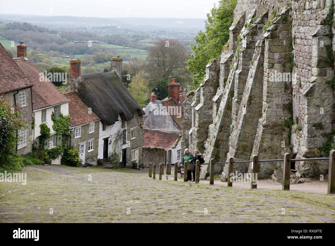 View down steep Gold Hill, with quaint and thatched roofed cottages in Shaftesbury, Dorset, England, UK - Stock Image