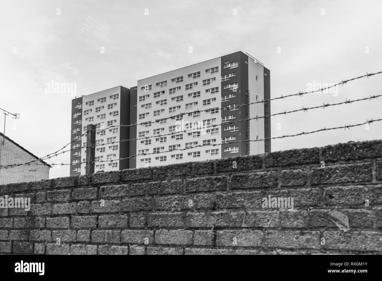 Monochrome of Shirley Towers a residential council owned concrete tower block seen through barbed wire, Shirley district, Southampton, England, UK - Stock Image