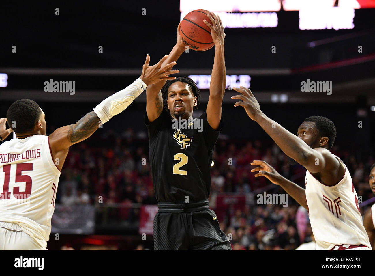 Philadelphia, Pennsylvania, USA. 9th Mar, 2019. UCF Knights guard TERRELL ALLEN (2) is defended by Temple Owls guard NATE PIERRE-LOUIS (15) and center ERNEST AFLAKPUI (24) during the American Athletic Conference basketball game played at the Liacouras Center in Philadelphia. Temple beat #25 UCF 67-62. Credit: Ken Inness/ZUMA Wire/Alamy Live News - Stock Image