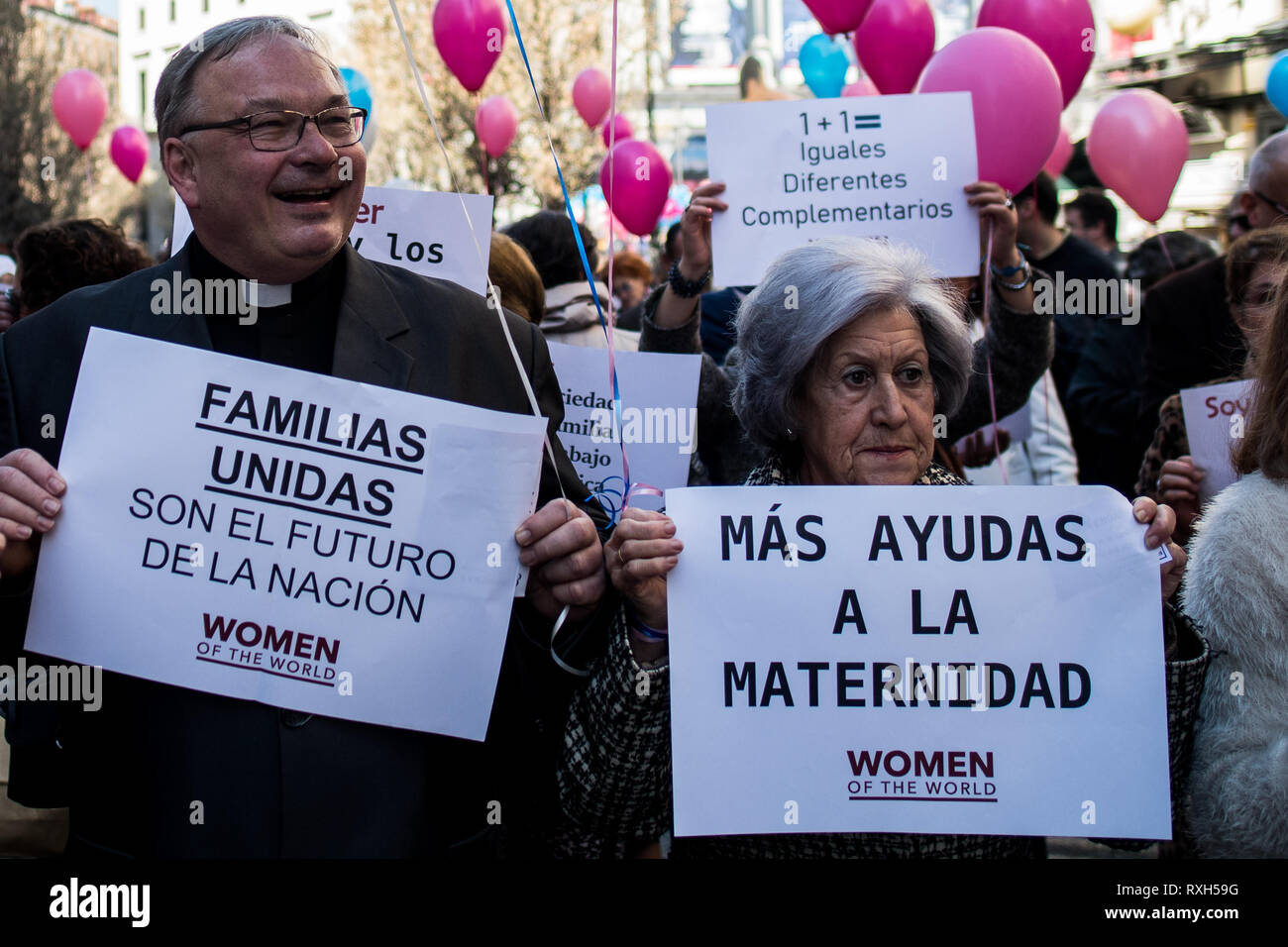 Madrid, Spain. 10th March, 2019. A priest protesting with a placard that reads 'United families are the future of the nation'. Conservative, far right wing and ultra Catholic groups demonstrate under the slogan 'In feminine yes, and masculine too' in a march organized by the platform 'Women of the World'. The protest against what they call 'supremacist feminism' is part of the activities of the International Women's Day. Credit: Marcos del Mazo/Alamy Live News - Stock Image