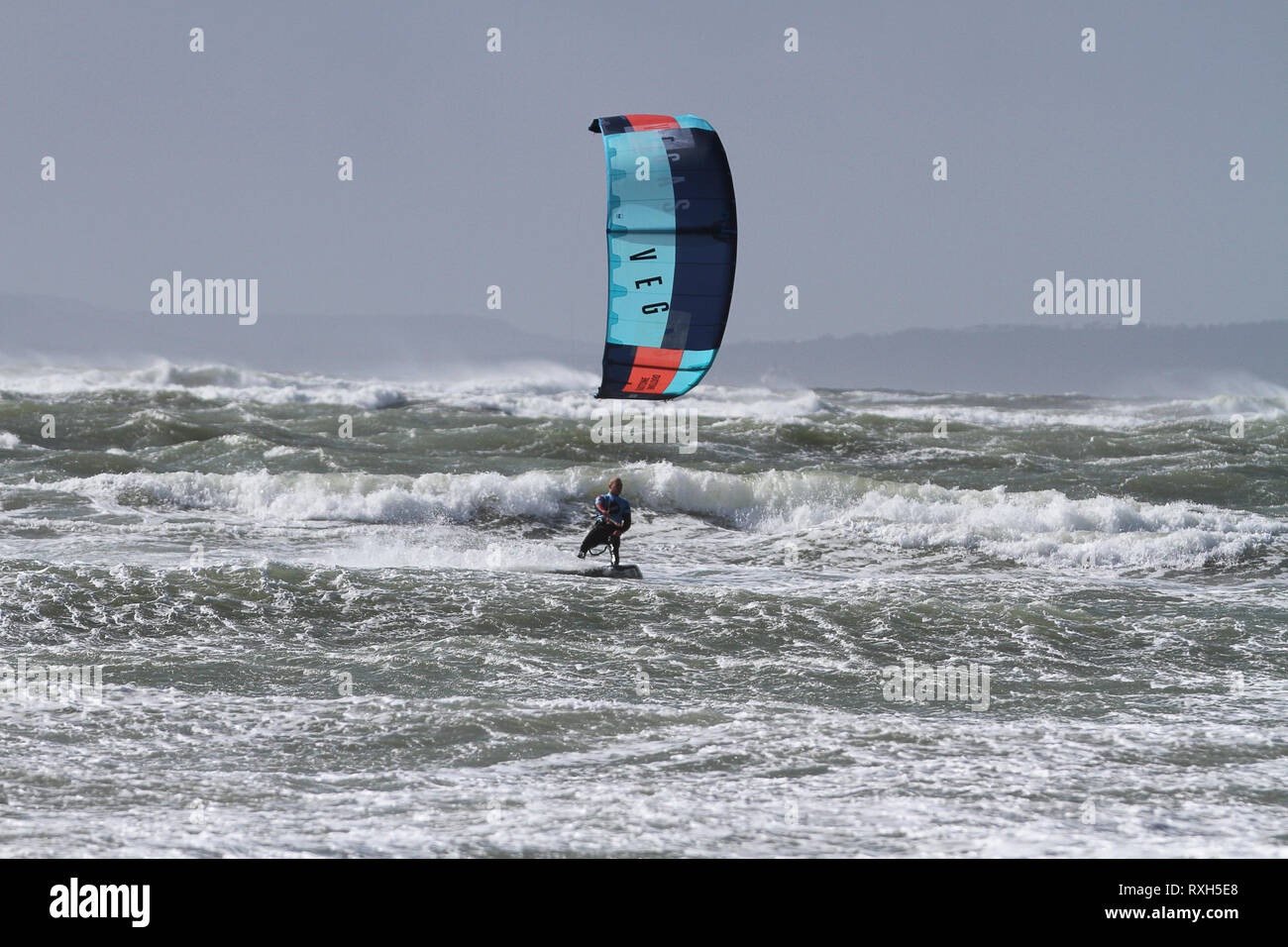 West Strand, West Wittering, Sussex, UK. 10th March 2019. Severe gales along the south coast today with gusts of over 60 mph. Four times British Champion Kitesurfer Lewis Crathern, famed for jumping his kitesurfer over Brighton Pier, in action at 2XS Watersports at West Wittering beach in West Sussex. Credit: james jagger/Alamy Live News - Stock Image