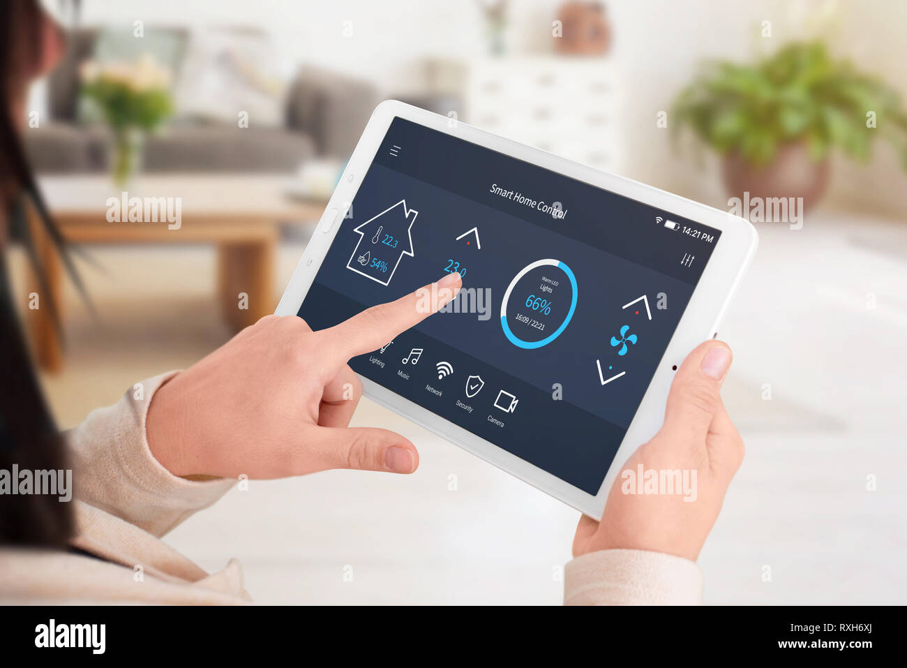 Modern software to home control on tablet display. Woman control temperature in living room. Close-up. - Stock Image