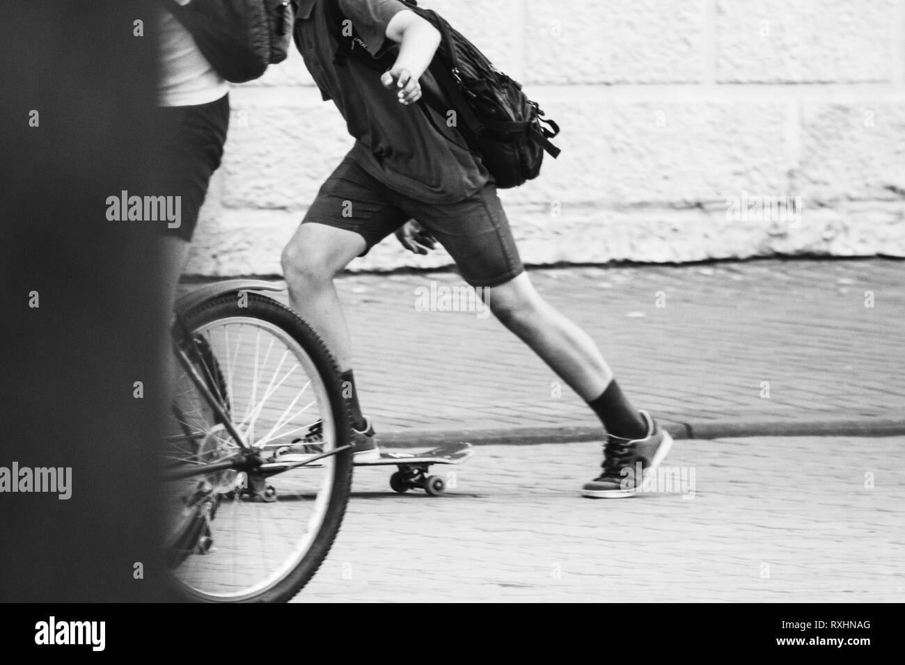 Skateboarding. Teen in shorts rides a skateboard. Black and white photography - Stock Image