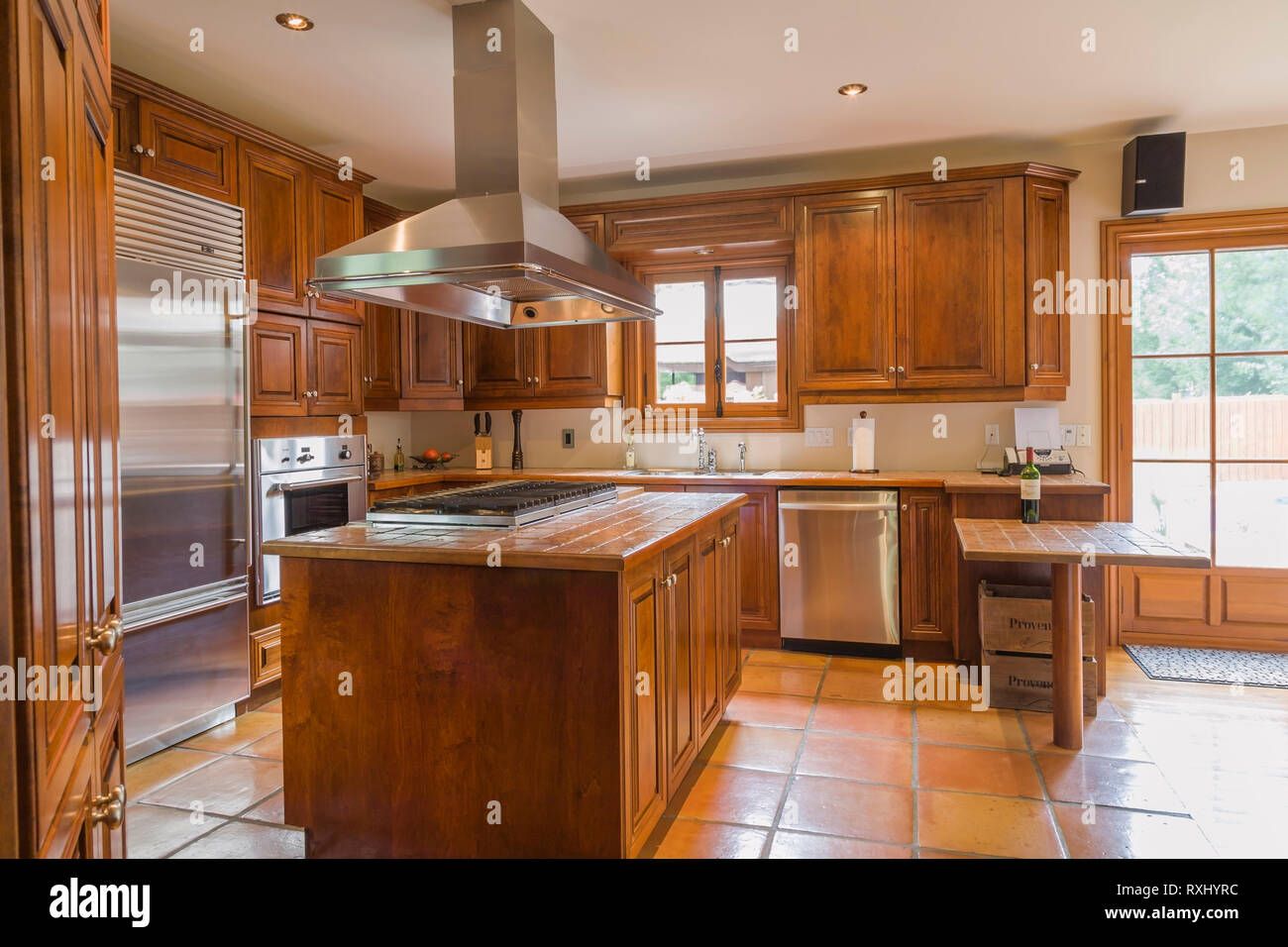 Maple Wood Cabinets And Island With Marble Tile Countertop In Kitchen With Terracotta Ceramic Tile Floor