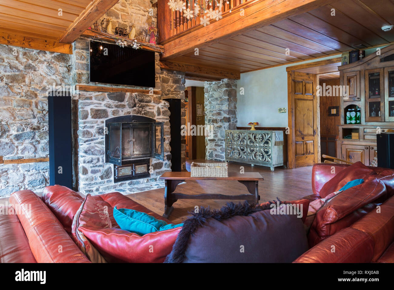reddish burgundy leather sofas with wooden bench style coffee tablereddish burgundy leather sofas with wooden bench style coffee table in living room with natural stone fireplace with wrought iron doors inside an old