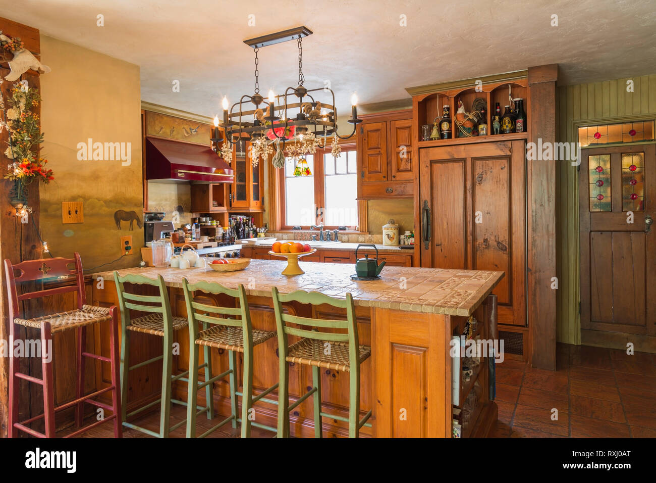 Stone and inlaid ceramic tile top pinewood island with wood and woven rawhide seat chairs and cabinets, Ultraline professional gas stove range hood an - Stock Image