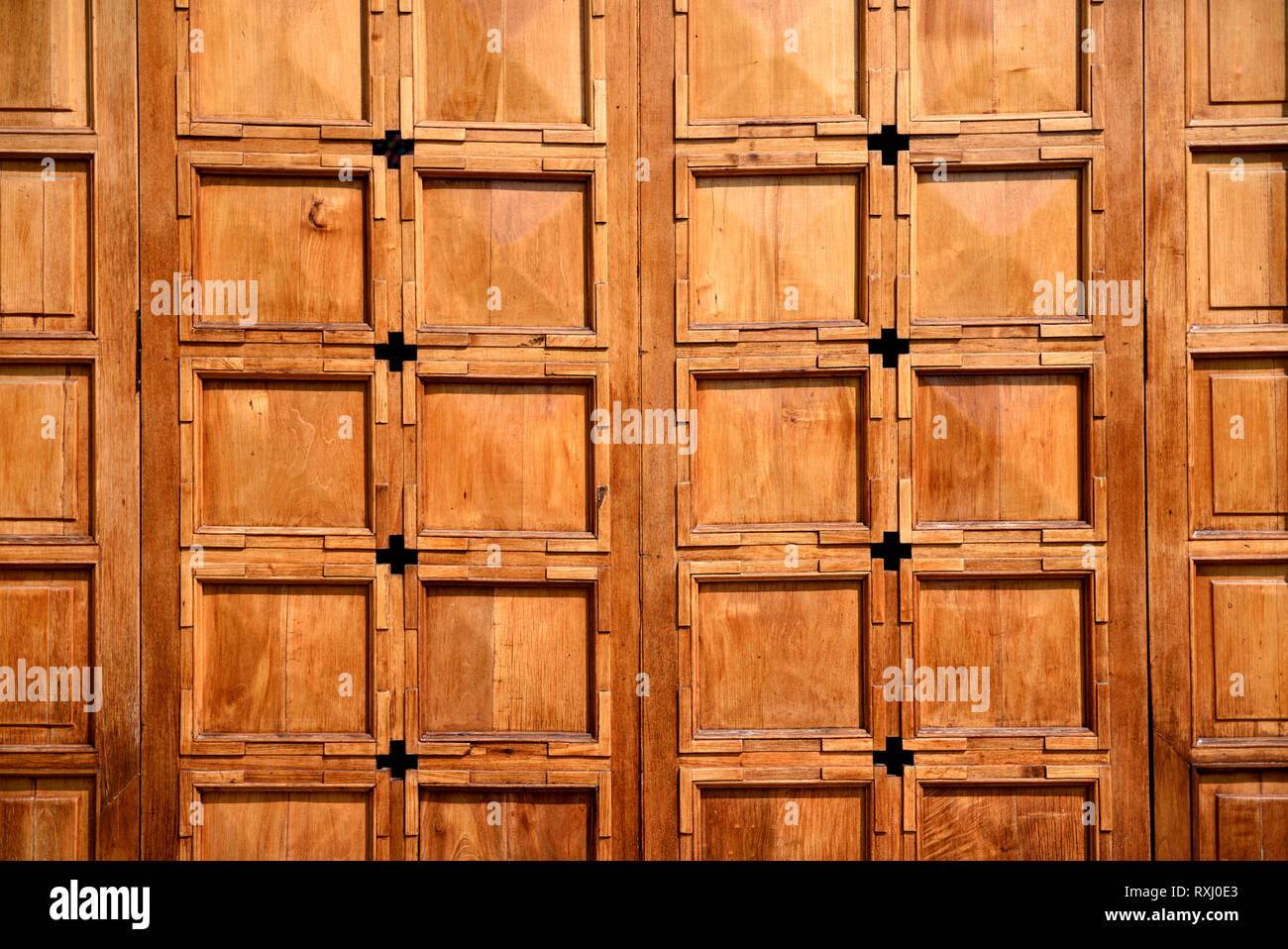 Sunlit wooden doors, square patterns with natural grains and textures. Stock Photo