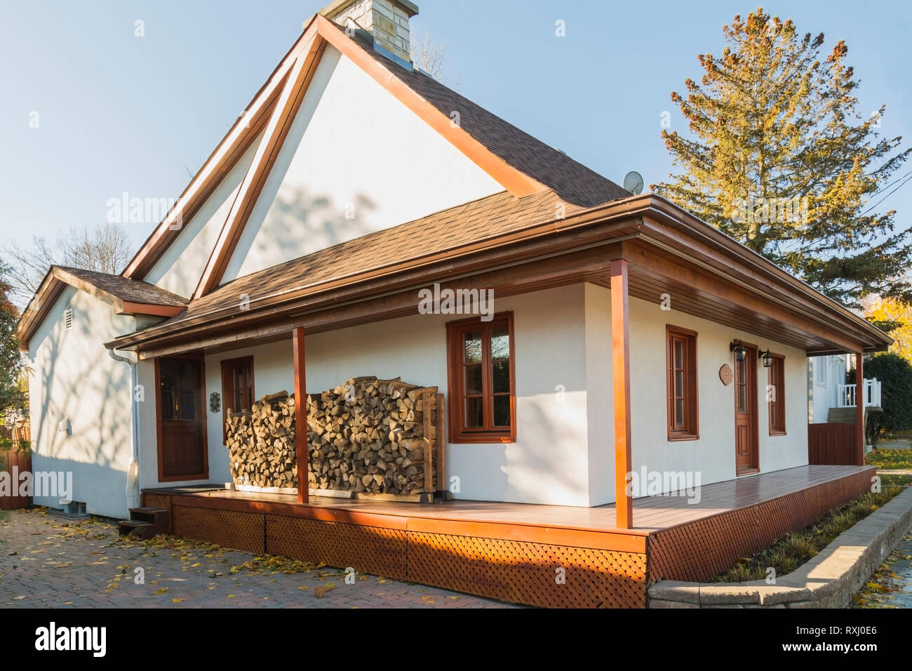 Old 1877 French regime style house facade with white stucco finish, reddish brown stained lattice-work and period reproduction wooden windows and cord - Stock Image