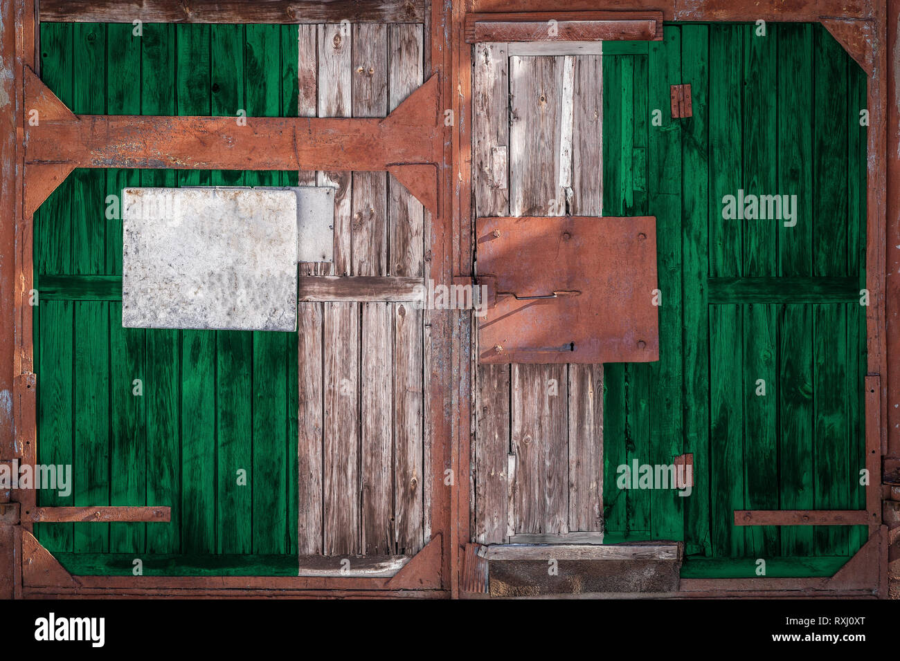 Close-up of old warehouse gate with national flag of Nigeria. The concept of export-import Nigeria, storage of goods and national delivery of goods. F - Stock Image
