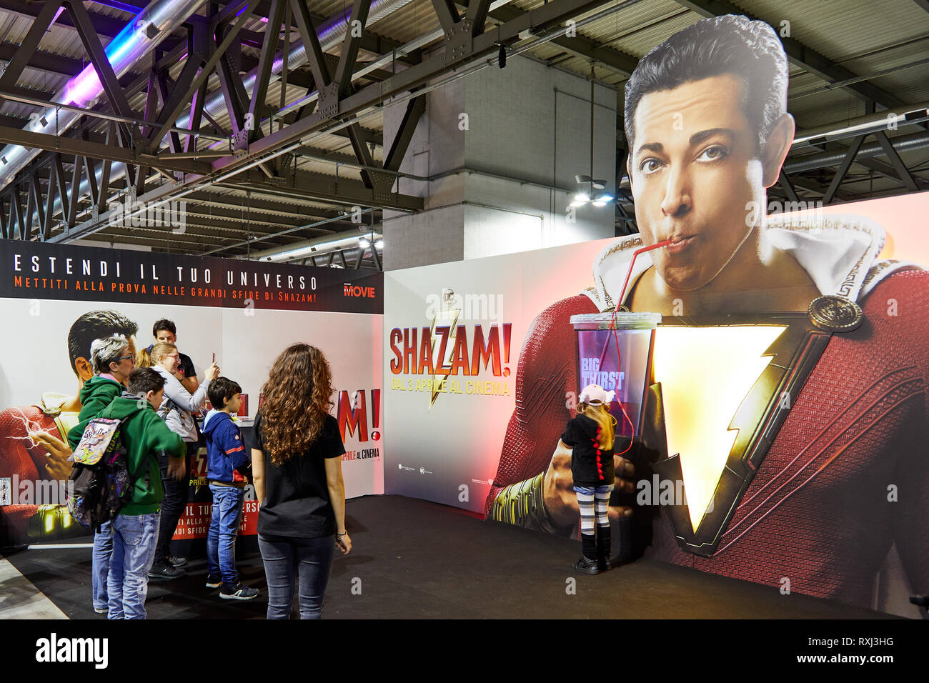 Milan, Italy - March 8 2019 Cartoomics Comic Con  visitors play and pose for photos at Shazam promotional stand - Stock Image