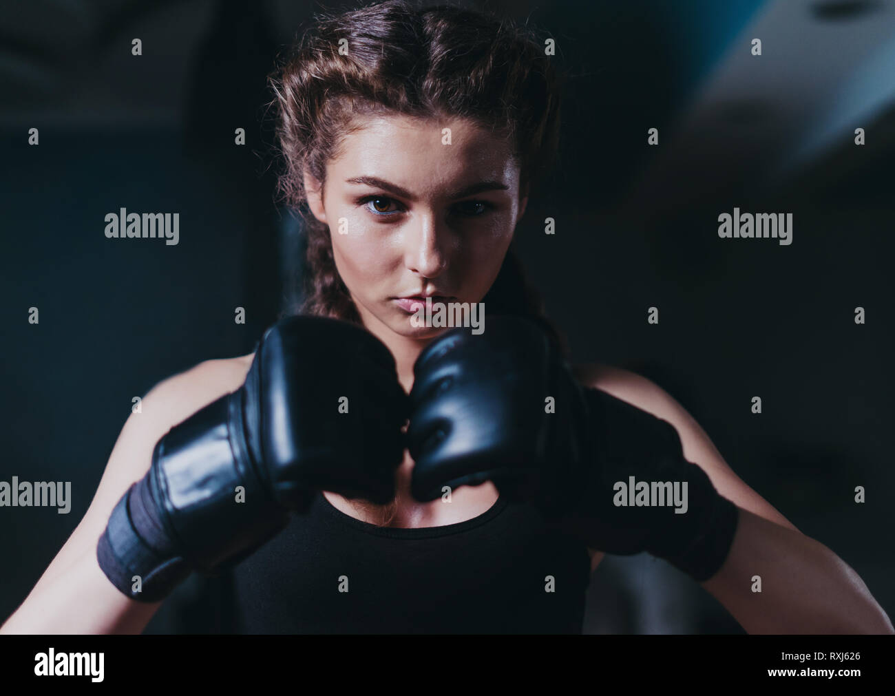 Young fighter boxer girl wearing boxing gloves before  training - Stock Image