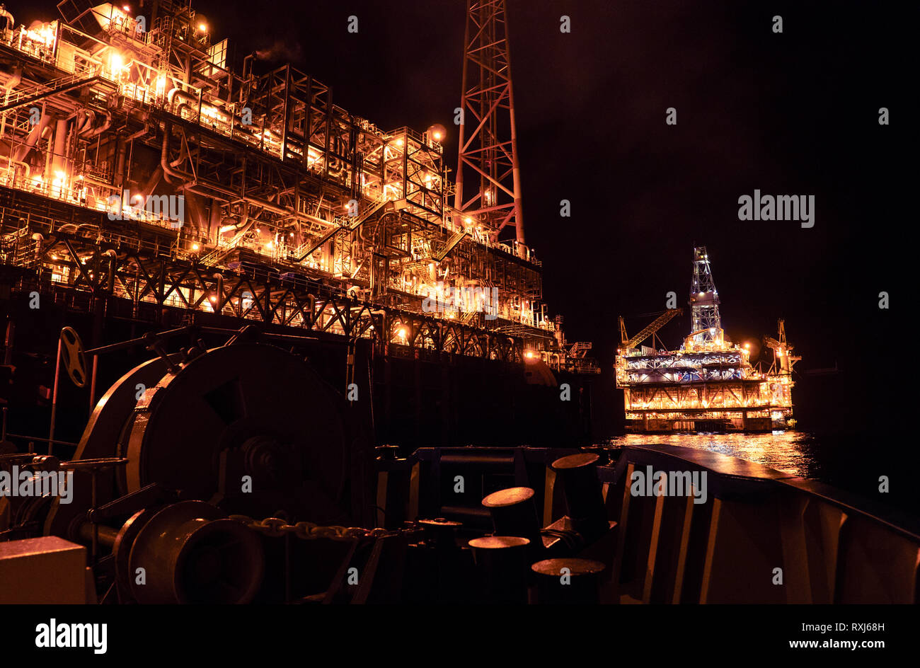 FPSO tanker vessel near Oil platform Rig at night. Offshore oil and gas industry Stock Photo
