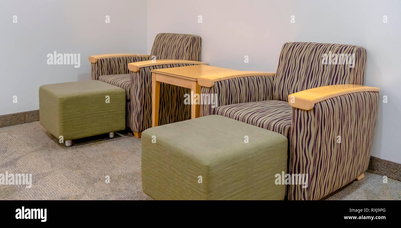 A Wooden table between armchairs with ottomans Stock Photo