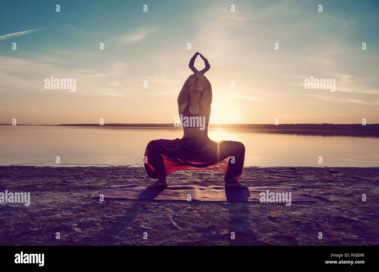 yoga woman on the beach at sunset. Stock Photo