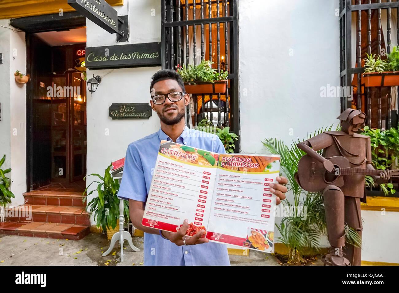 Cartagena Colombia Old Walled City Center centre Getsemani Hispanic man Casa de las Palmas restaurant host manager offering menu Spanish language - Stock Image