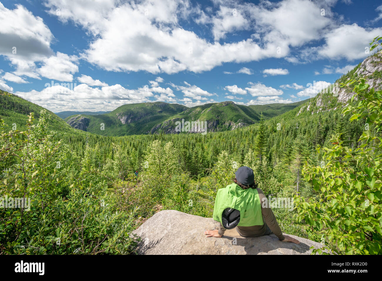 Single hiker man resting and looking at a beautiful mountain view in Les Grands-Jardins National Park, province of Quebec, Canada - Stock Image