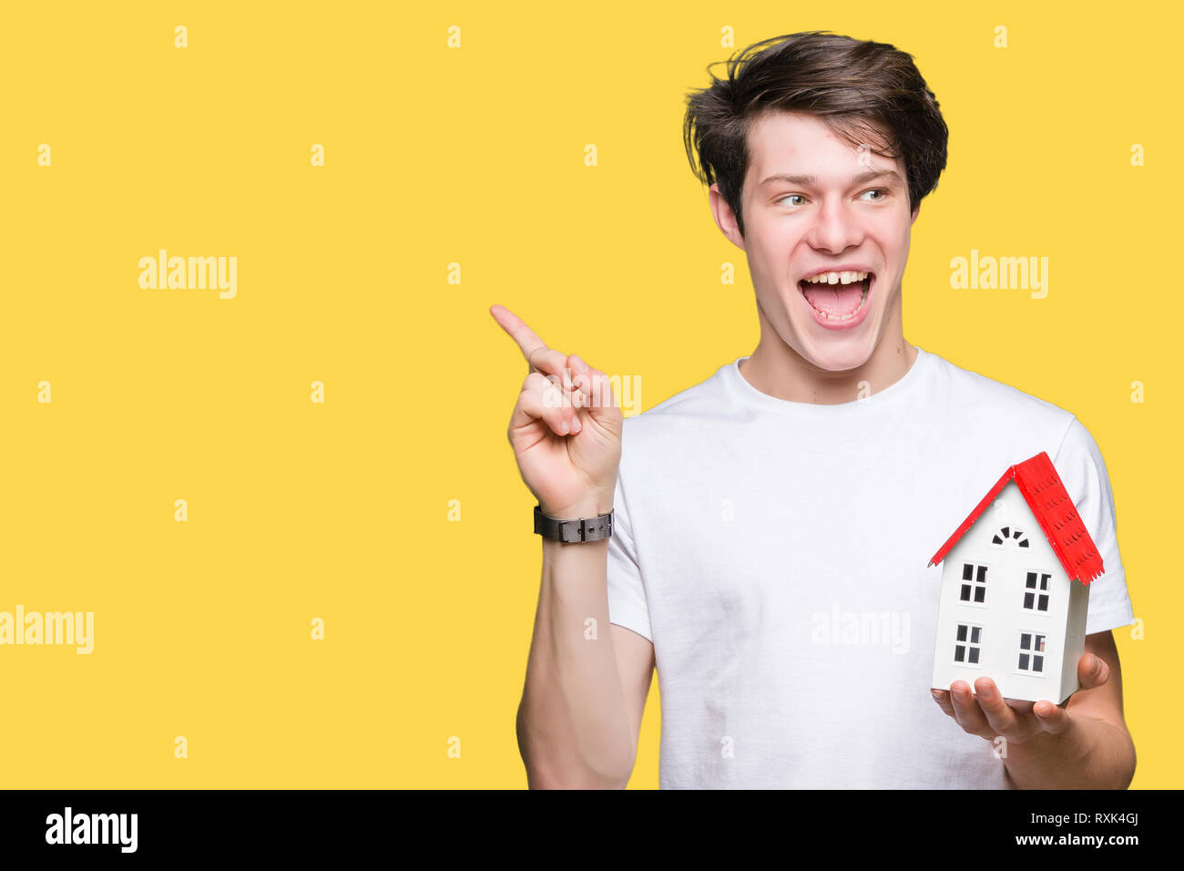 Young man holding house over isolated background very happy pointing with hand and finger to the side - Stock Image