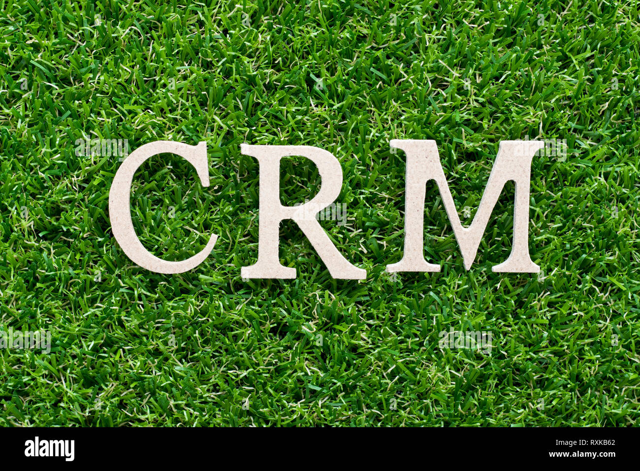 Wood alphabet in word CRM (abbreviation of Customer Relationship Management) on artificial green grass background - Stock Image