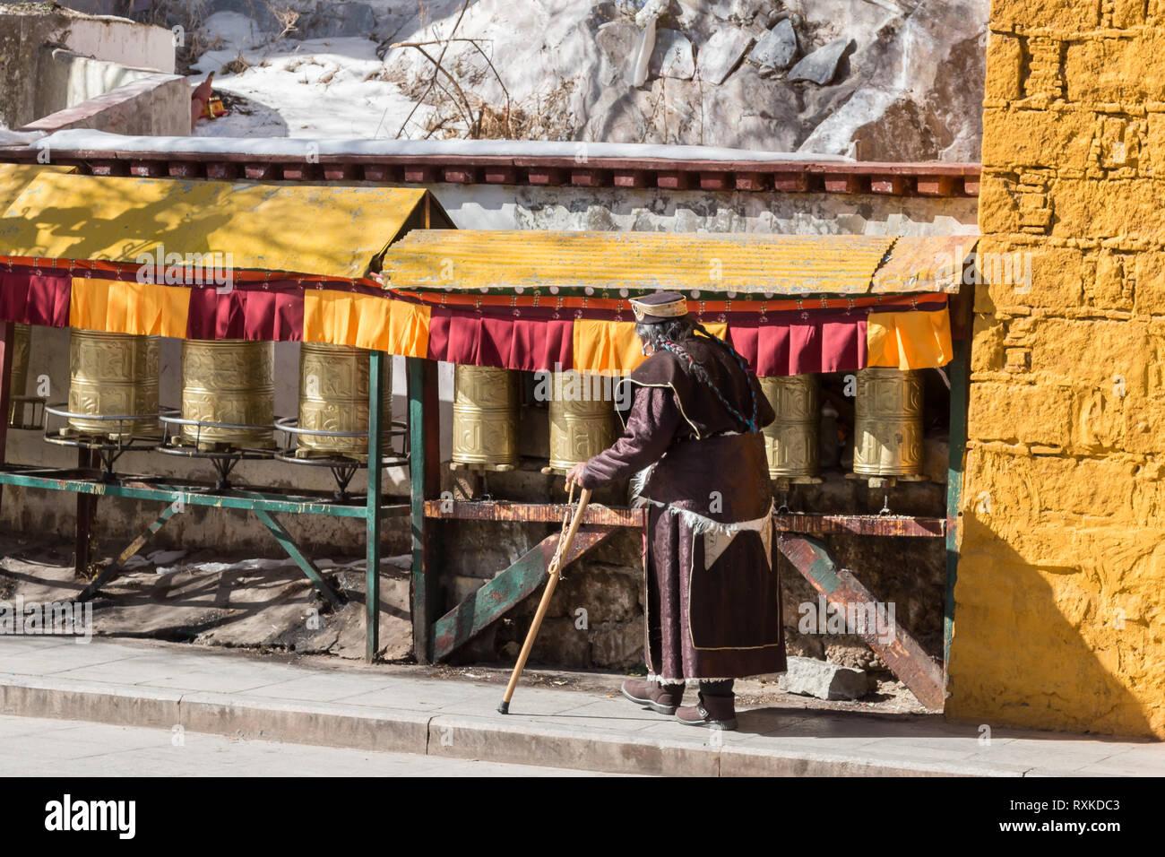 An old Buddhist man worshiping by spinning prayer wheels at Potala Palace, Lhasa, Tibet. - Stock Image