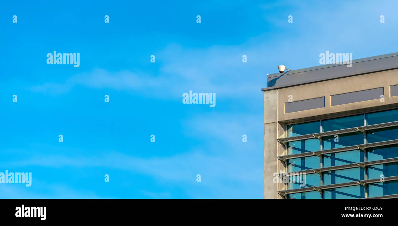 Surveillance video camera at the top of a building - Stock Image