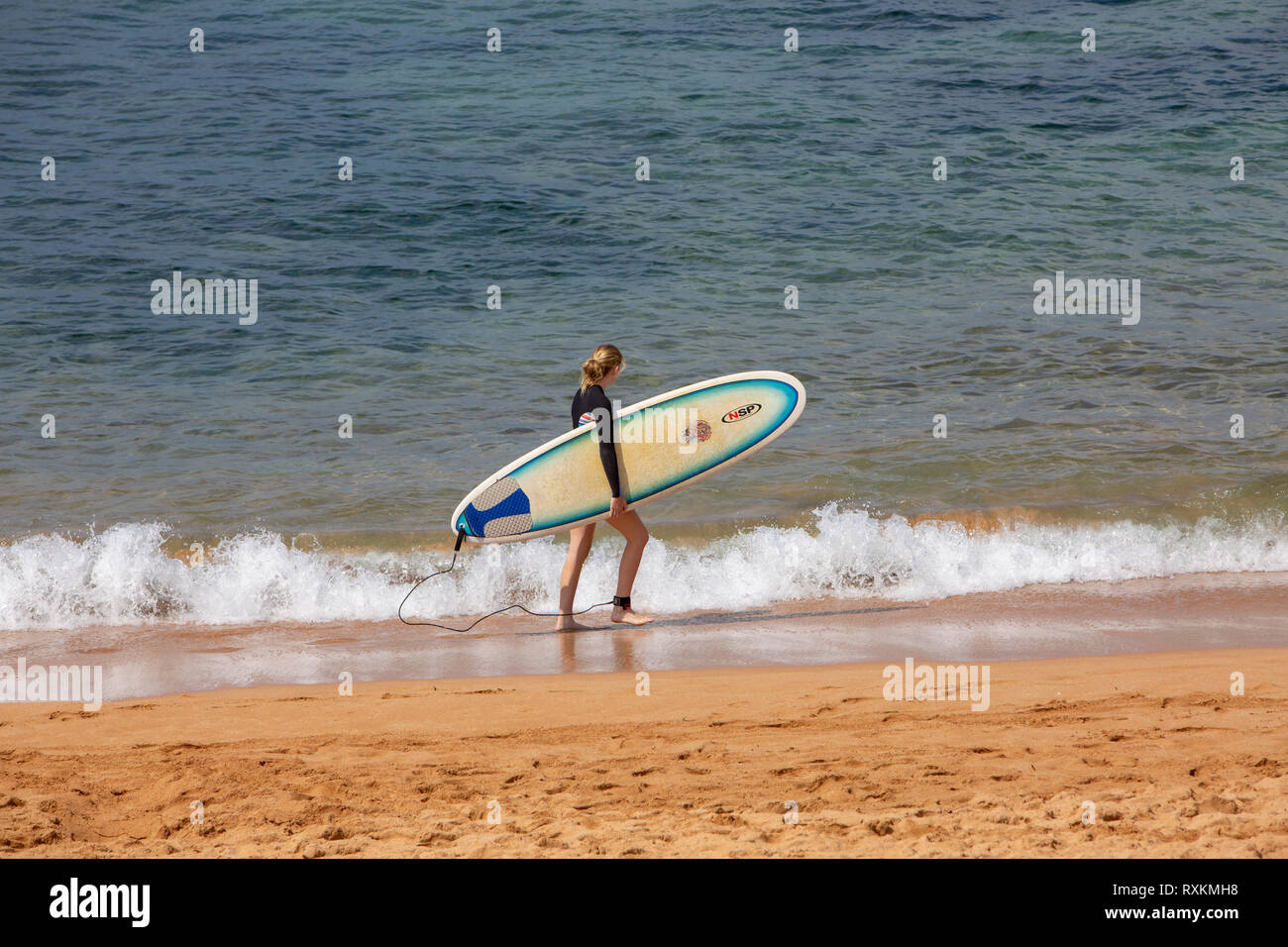 Blonde girl carries her surfboard along the beach in Sydney,Australia - Stock Image